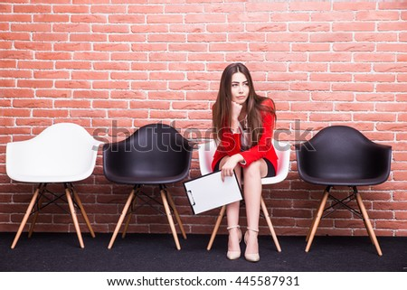 Bored young businesswoman holding paper and looking away while sitting on chair - stock photo