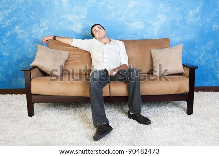 Bored young Caucasian man on sofa looks up - stock photo
