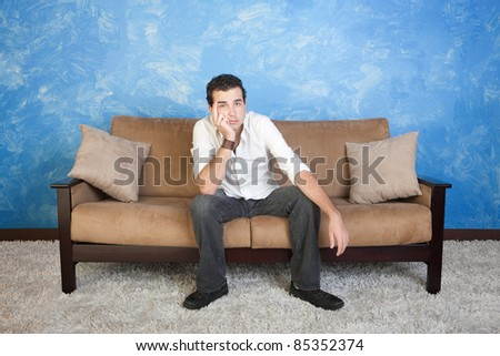 Bored young Caucasian man sits on sofa with hand on face - stock photo