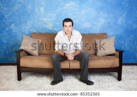 Bored young Caucasian man with hands clasped relaxes on sofa - stock photo