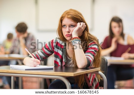 Bored young female student with others writing notes in the classroom - stock photo