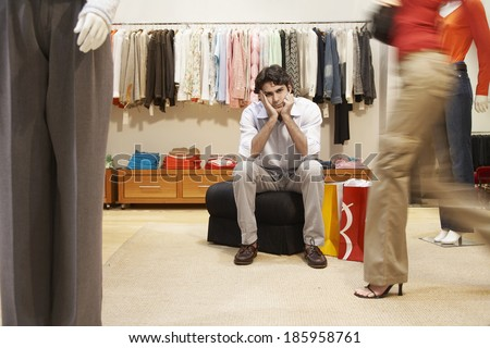Bored young man in women's clothing store - stock photo
