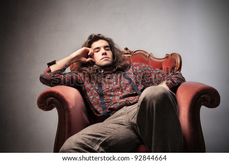 Bored young man sitting on an armchair - stock photo
