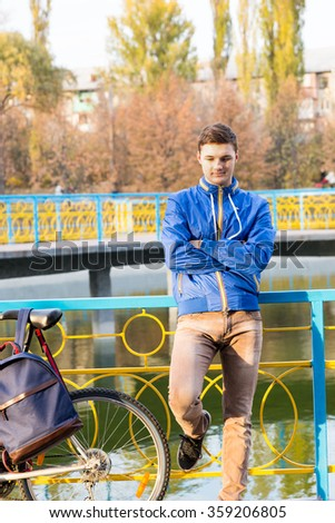 Bored young man standing waiting with folded arms leaning back against colorful iron railings above a lake or canal with his bike alongside - stock photo