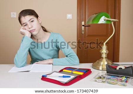 Bored young woman at desk with workbook and pencil