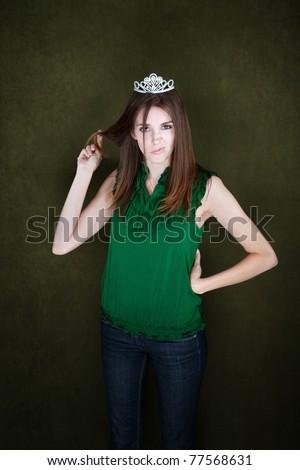 Bored young woman wearing a tiara twirls her hair - stock photo