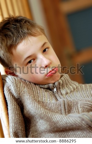 Boredom - sadly expression of young boy - stock photo