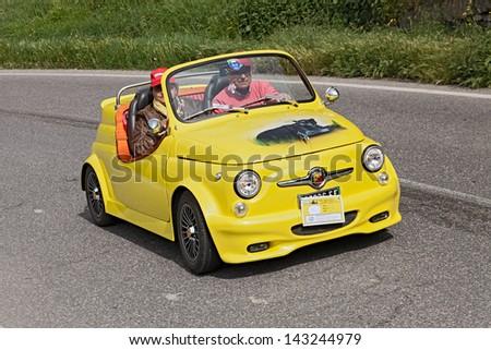 "BORGO RIVOLA (RA), ITALY - MAY 1: unidentified crew on a yellow tuned car Fiat 500 Abarth roadster in rally for vintage cars ""Raduno colline di cristallo"" on May 1, 2013 in Borgo Rivola, RA, Italy - stock photo"