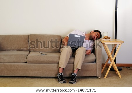 Boring computer nerd falls asleep on couch while using internet - stock photo