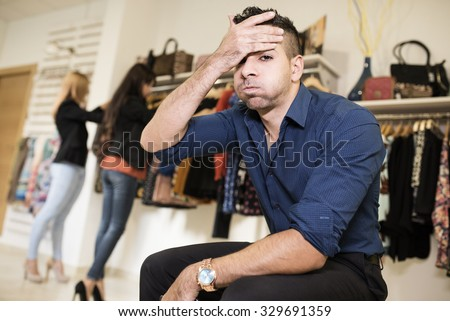 Boring man waiting his girlfriends end shopping session