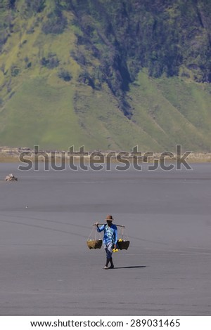 BORMO - JUNE 13, 2015: Local fruits seller passing by Tengger Sand Sea, Bromo Indonesia - stock photo