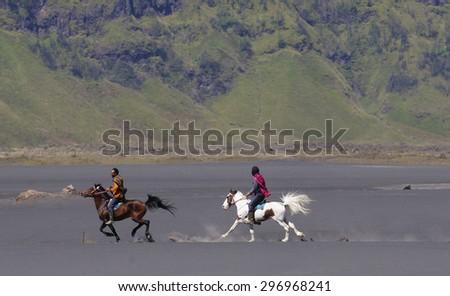 BORMO - JUNE 13, 2015: Tengger horsemen in horse racing at The Tengger Sand Sea, Bromo Indonesia - stock photo