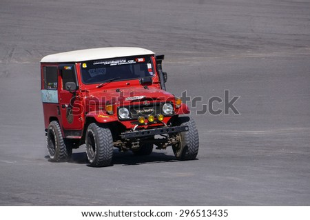 BORMO - JUNE 13, 2015: 4x4 jeep passing by at The Tengger Sand Sea, Bromo Indonesia. Jeep is the main transportation in Bromo and available for rent. - stock photo