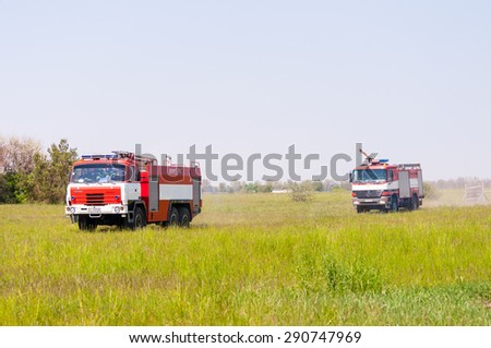 BORYSPIL, UKRAINE - MAY, 20, 2015: Fire-brigade on firetruck Tatra and Mercedes ride on alarm for instruction for fire suppression and mine victim assistance at Boryspil International Airport, Kiev - stock photo