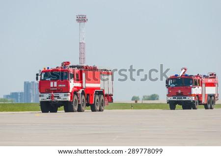 BORYSPIL, UKRAINE - MAY, 20, 2015: Two red firetruck Kamaz and Tatra ride on call fire suppression and mine victim assistance at Boryspil International Airport, Kiev, Ukraine.  - stock photo