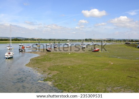 Bosham in West Sussex. England. At low tide with moored and beached boats - stock photo