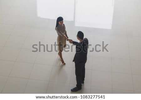 Boss secretary shaking hands greet each stock photo royalty free boss and secretary are shaking hands to greet each other at the lobby of the office m4hsunfo
