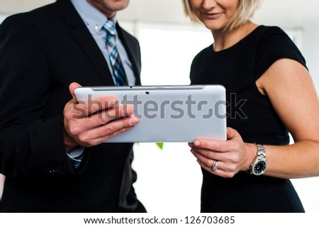 Boss and secretary posing with a tablet device, cropped image. - stock photo