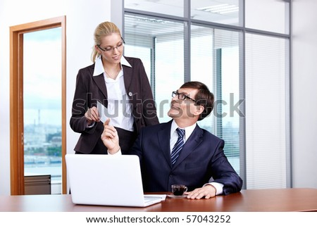Boss gives the envelope to the secretary in the office - stock photo