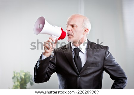 boss giving orders to his employees in a very bossy way - stock photo