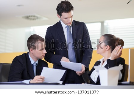 Boss is unsatisfied with the work done by his employees - stock photo