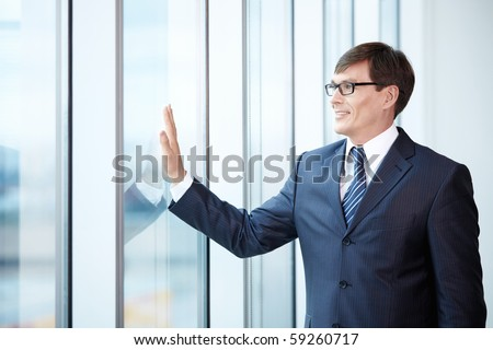 Boss looks out the window in the office - stock photo