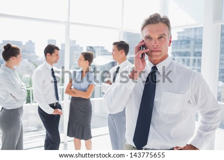 Boss on the phone standing in a modern office with colleagues behind - stock photo