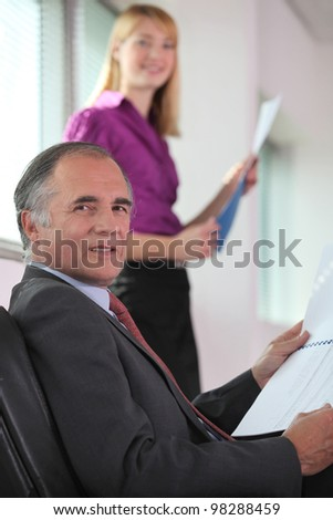 Boss running through presentation with assistant - stock photo