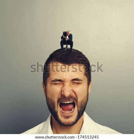boss screaming at big businessman over dark background - stock photo
