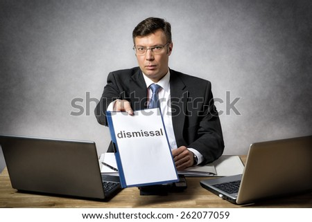 Boss sitting at the desk in office dismiss somebody - stock photo