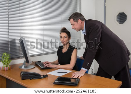 Boss standing in the office looking at the computer with his secretary
