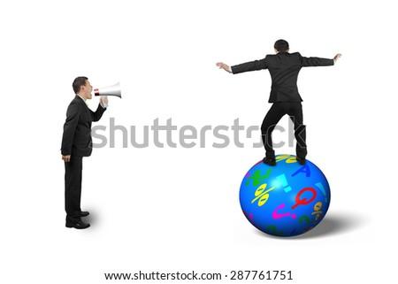 Boss using speaker yelling at businessman balancing on the colorful symbols ball, isolated on white background. - stock photo