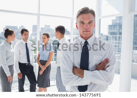 Boss with arms folded standing in a modern office with colleagues behind - stock photo