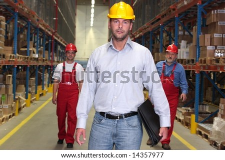 boss with briefcase at the front of team of workforce in warehouse - 2 or 3 workers in background - stock photo