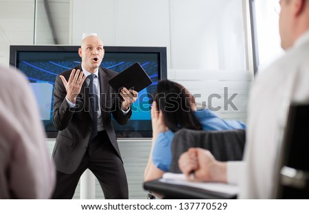 Boss yelling at his employees at a briefing - stock photo