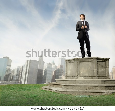 Bossy businessman on a pedestal with cityscape on the background - stock photo