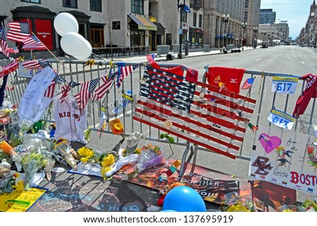 BOSTON - APR 20: Flowers on memorial set up on Boylston Street in Boston, USA on April 20, 2013. 3 people killed and over 100s injured during Boston Marathon bombing on April 15, 2013. - stock photo