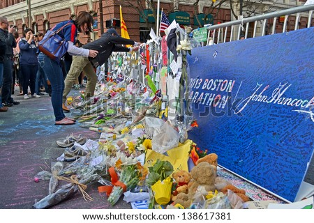 BOSTON - APR 20: People poured over the memorial set up on Boylston Street in Boston, USA on April 20, 2013. 3 people killed and over 100s injured during Boston Marathon bombing on April 15, 2013. - stock photo