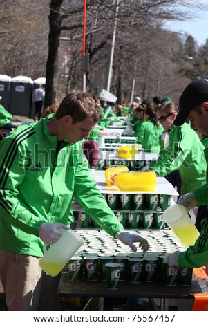 BOSTON - APRIL 18 : Volunteers gave water to runners during the Boston Marathon on April 18, 2011 in Boston. Geoffrey Mutai (Kenya) finished first with a time of 2:03:02. - stock photo