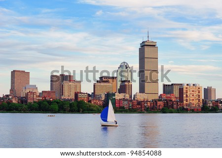 Boston city skyline with Prudential Tower and urban skyscrapers over Charles River with boat. - stock photo