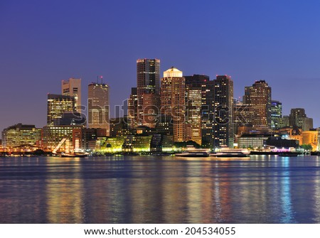 Boston downtown skyline panorama with skyscrapers over water with reflections at dusk illuminated with lights.