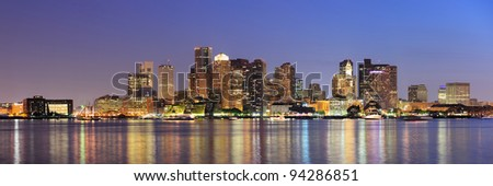 Boston downtown skyline panorama with skyscrapers over water with reflections at dusk illuminated with lights. - stock photo