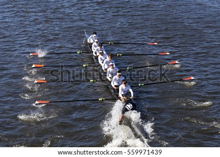 BOSTON - OCTOBER 23, 2016: Winter Park Crew coxswain Sean Kerns puts hand in water in order to turn quickly in the Head of Charles Regatta Men's Youth Eights [PUBLIC RACE]