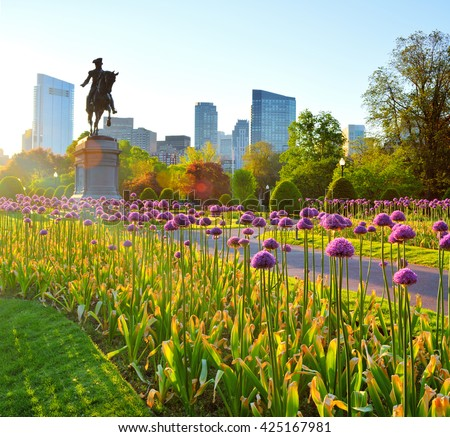 Boston Public Garden at dawn. George Washington statue and city skyline in background