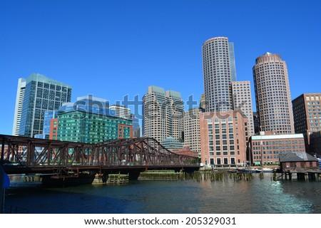 Boston skyline and Northern Avenue Bridge along Boston Harbor. - stock photo