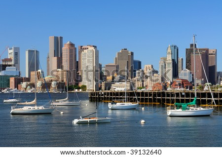 Boston skyline from East Boston. Old dock and sailboats in foreground, modern office and apartment buildings in background.
