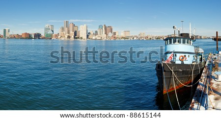 Boston skyline panorama with old boat in the foreground. - stock photo