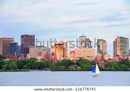 Boston sunset over Charles River with urban skyscrapers and boat. - stock photo
