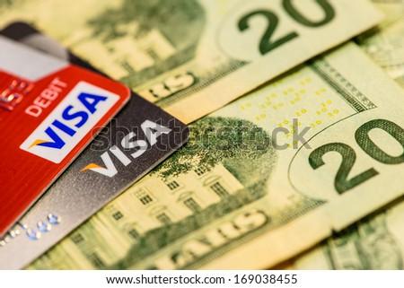 BOSTON, USA - DECEMBER 29, 2013: Visa Credit and Debit Cards Over Dollar bills - stock photo