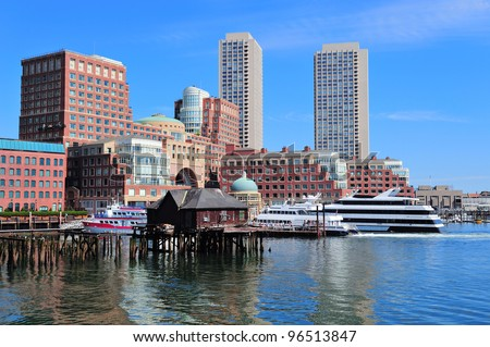 Boston waterfront with skyscrapers and boat in the morning.
